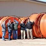Staff in front of fiber optic spools.